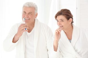 mature couple brushing teeth